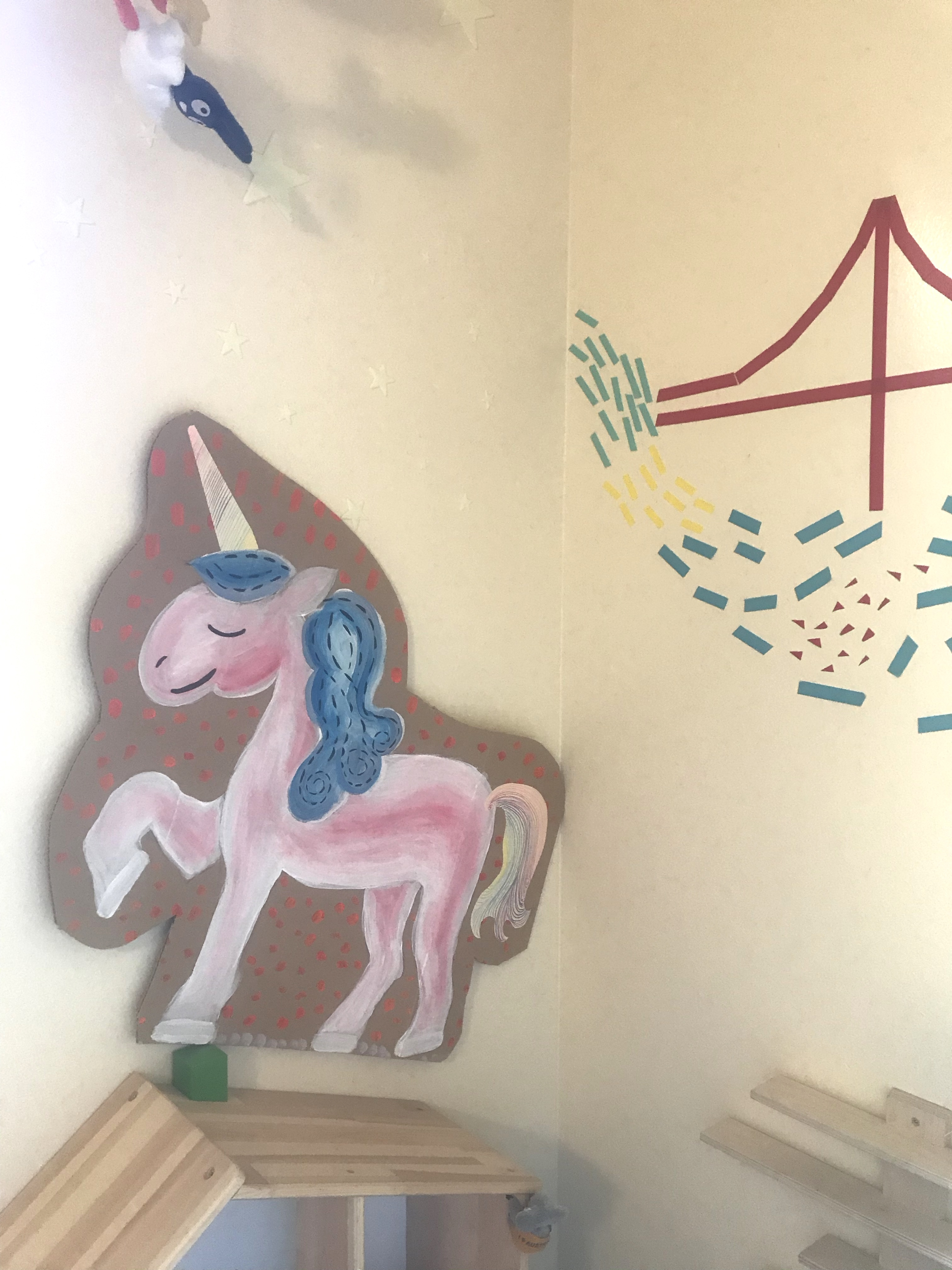 unicorn painted on cardboard, cut out, on wall above dollhouse